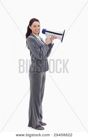 Profile of a businesswoman smiling with a megaphone against white background