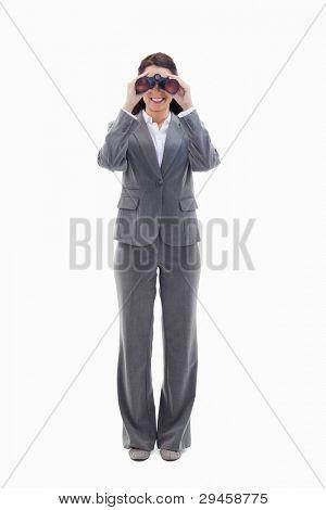 geschäftsfrau lächelnd und looking through Binoculars against white background