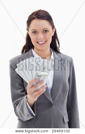 Close-up of a businesswoman smiling and holding a lot of dollar bank notes against white background