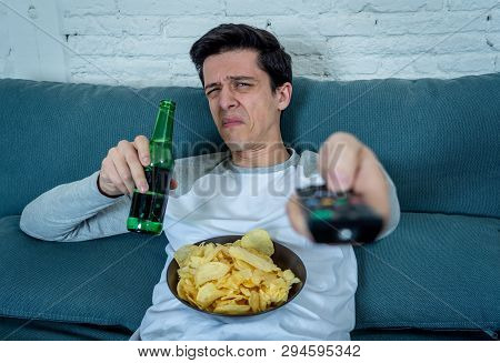 Portrait Of A Young Man Looking Scared And Shocked Watching Tv. Human Expressions And Emotions