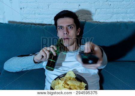 Young Man Looking Scared Sitting On Sofa Watching Horror Movie On Tv At Night.