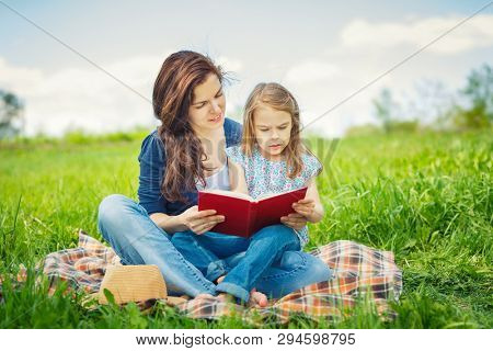 Mother and daughter enjoy reading book sitting on green meadow in the summer park