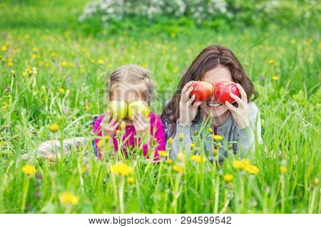 Mother and daughter lying on green meadow and holding apples