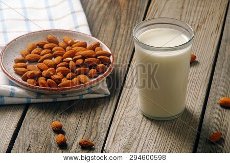 Glass Of Almond Milk With Almond Nuts On Rustic Wooden Table. Vegan Alternative Food, Non-dairy Milk