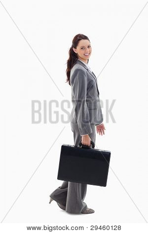 Profile of a business woman smiling and walking with a briefcase against white background