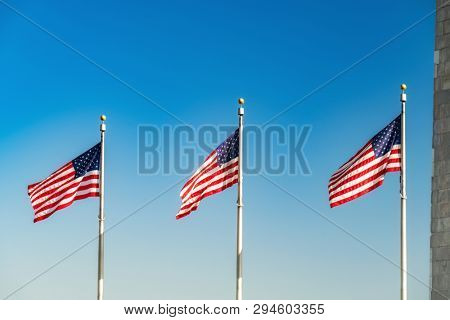 Flags of the United States waving over blue sky in Washington DC