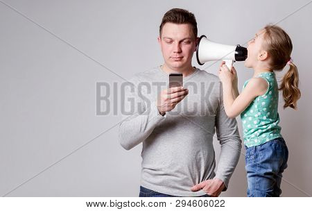 Father Using Smartphone Ignoring His Daughter, Child Tries To Attract Attention To Himself, The Pare