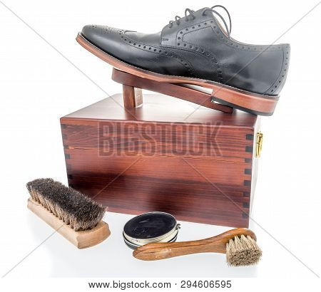 A black shoe on a shoe polish box that is ready to be shined with shoe polish, dauber and brush poster