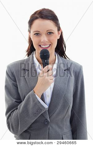 Close-up of a businesswoman smiling and holding a microphone against white background