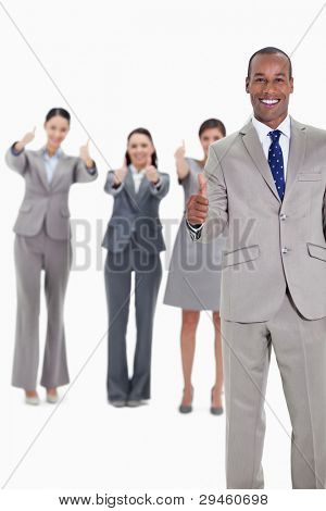 Business team smiling with thumbs up and with one businessman in foreground