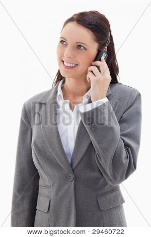 Businesswoman looking up while smiling on the phone against white background