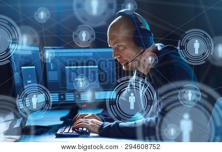 cybercrime, hacking and technology concept - male hacker in headset with progress loading bar on computer screen wiretapping or using virus program for cyber attack in dark room poster