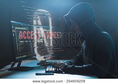 cybercrime, hacking and technology concept - male hacker with access denied message on computer screen using virus program for cyber attack in dark room