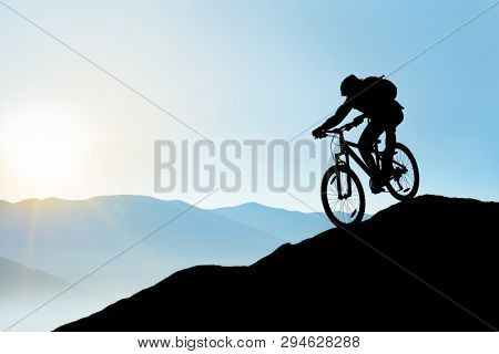 Silhouette of Cyclist Riding the Bike in the Beautiful Mountains Down the Rock on the Sunrise Sky Background. Extreme Sport and Enduro Biking Concept.