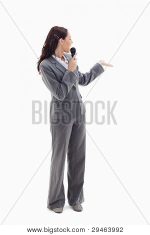 Businesswoman announcer speaking in a microphone and looking behind against white background