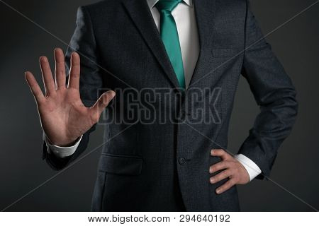 Business Man Is Showing A Stop Gesture By His Hand On A Gray Background. Shut Up Gesture. Stop Talki