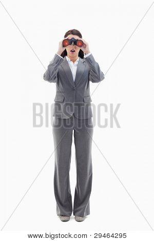 Surprised businesswoman looking through binoculars against white background