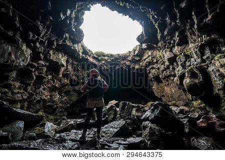 Woman Traveler Explore Lava Tunnel In Iceland.