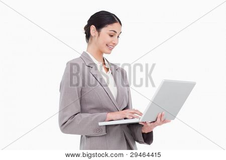 Side view of businesswoman using laptop against a white background