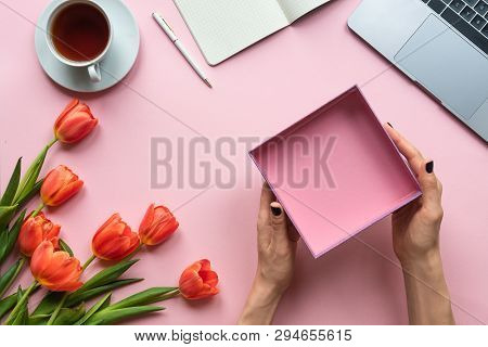 Female Hands With Open Empty Box On Pink Background. Background With Coffee, Laptop And Tulpi