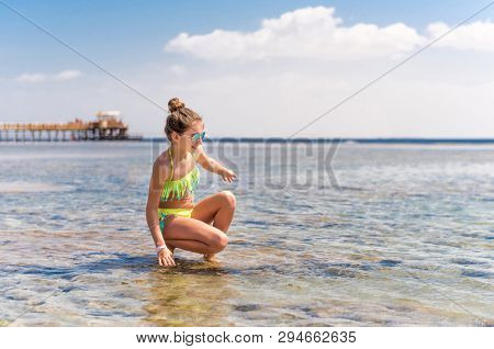 Beatiful funny teenage girl splashing warm sea water at beach
