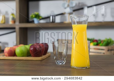 Close Up Image Of A Jug Of Freshly Squeezed Orange Juice And Drinking Glass On The Dark Wooden Table