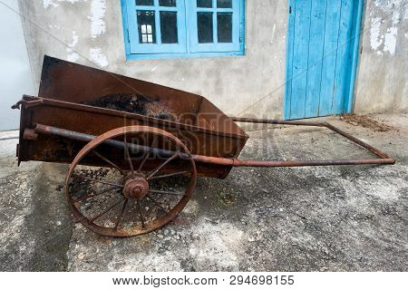Old Farm Cart With Two Whells Standing Near House.