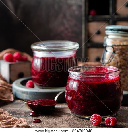 Two Glass Jars With Homemade Dark Red Jam Or Jelly Standing On Brown Concrete Table With Raspberries