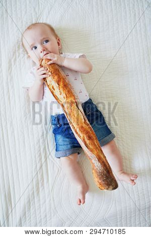 Six Months Old Baby Girl Eating Traditional French Bread (baguette). Introducing Solids To Infant Ki