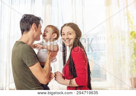 Happy Parents Father And Mother Playing With Baby Son At The On Window Background. Cheerful And Mode