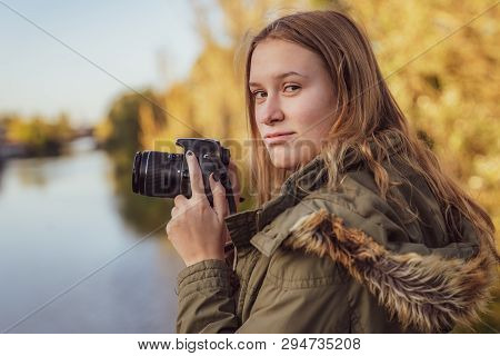 Young Woman With Slr Camera In His Hand Is Looking Into Camera
