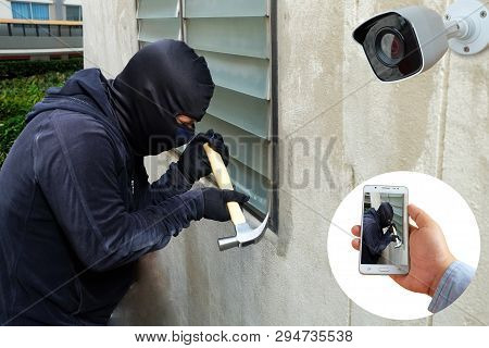 Surveillance Camera Capture And Record Caught Masked Thief With Hammer And Hand Holding Mobile Phone