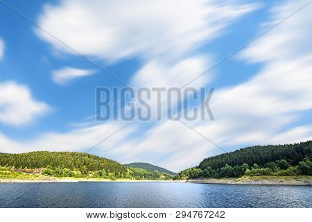 Large Lake Under A Blue Sky In The Wind With Forest On The Shore In The Summer