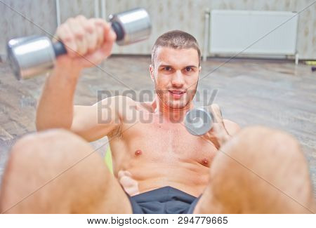 Young Handsome Man Doing A Curl For Abdominals With Dumbbells In His Hands. Strength Training Of Abd