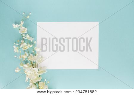 Mothers Day Or Wedding Floral Card With Paper Note And White Flowers Over A Blue Background Shot Fro