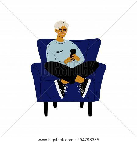 Young Man Sitting In Armchair With Smartphone, Guy Spending Weekend At Home And Relaxing, Rest At Ho