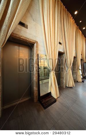 Several doors of lifts and long yellow curtains in empty hallway