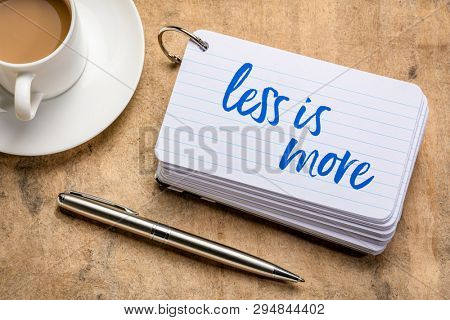 less is more - handwriting on a stack of index cards with a cup of coffee and  a pen, minimalism concept