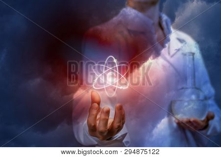 A closeup of a laboratory assistant with a flask in one hand is holding an atom in the other at the dark background. Innovative researches and medicine correlation concept. poster