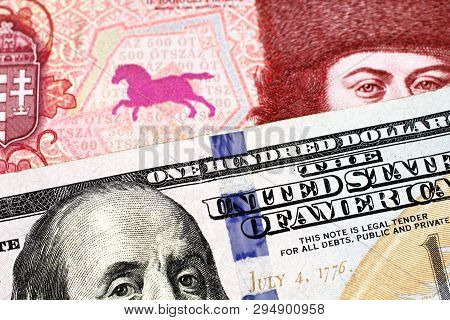 A Red, Five Hundred Hungarian Forint Bank Note With A Blue American One Hundred Dollar Bill Close Up
