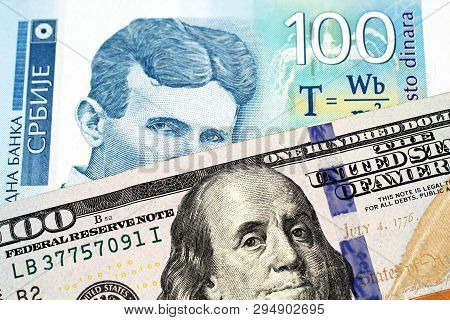 A Close Up Image Of A Blue One Hundred Serbian Dinar Bank Note With An American One Hundred Dollar B