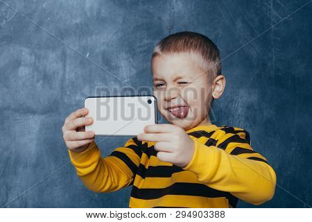 Little Cute Boy With A Mobile Phone Takes A Selfie And Shows Emotions On A Blue Background