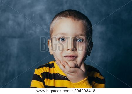 Portrait Of A Thoughtful Cute Little Child With Hand Touching Face, Looking At Camera Against Blue C