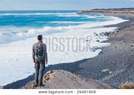 Young man hiking and looking up to the sea