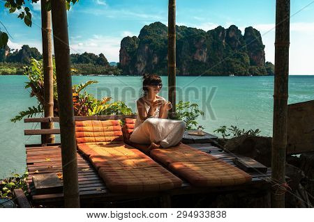 Beautiful Girl Resting On The Sea. Lonely Girl Resting On The Island. The Girl On The Paradise Coast