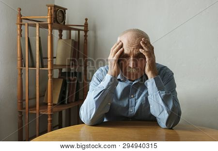 Worried Elderly Man With His Head In His Hands Seated At A Table Indoor Staring Dejectedly Ahead Wit