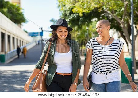 Young smiling women walking and talking while looking at each other outdoor. Happy best friends laughing and having fun while walking on city street. Two women friends sightseeing in summer.