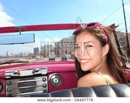 Car woman smiling happy on passenger seat in pink vintage convertible car. Young mixed race Asian / Caucasian female model during cuba vacation. Driving on Malecon waterfront, Havana, Cuba