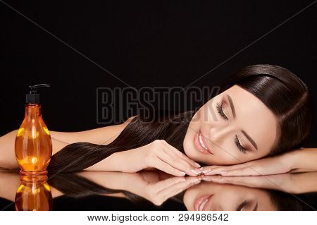 Beautiful Woman On Black Glass With Hair Oil