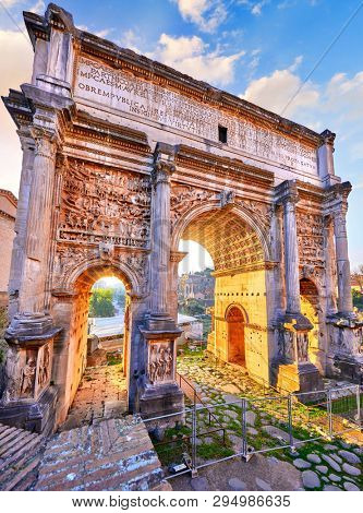 Antique Triumphal Arch in ancient Rome, Italy. Roman Forum. Ancient roman structure. Sunny light through arch sunrise early morning. Famous landmark in Roma old town.